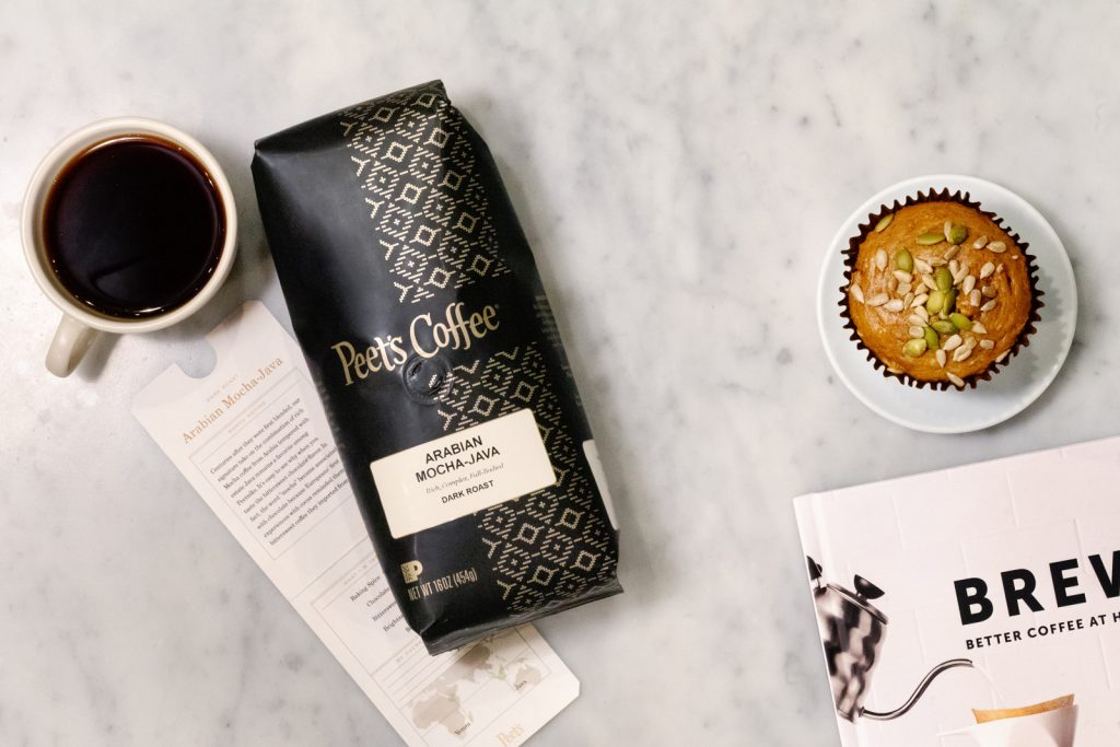 An overhead photo of a cup of Peet's Arabian Mocha Java, a bag of Peet's Arabian Mocha Java from the Peet's Signature Blend Coffee Subscription series, and an informational sheet with the coffee story, flavor notes, and cupping notes that comes with each shipment. Also, a muffin.